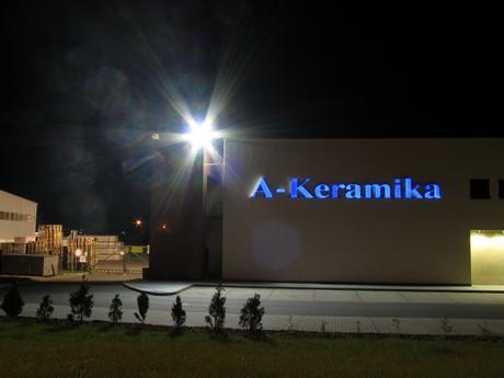 Silný halogenidový světlomet na budově firmy ozařuje zcela prázdné parkoviště
